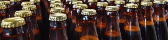 a photo of glass beer bottles on a bottling line in a brewery - encompass solutions.