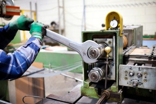 An image of a factory maintenance worker adjusting a machine with a large wrench.