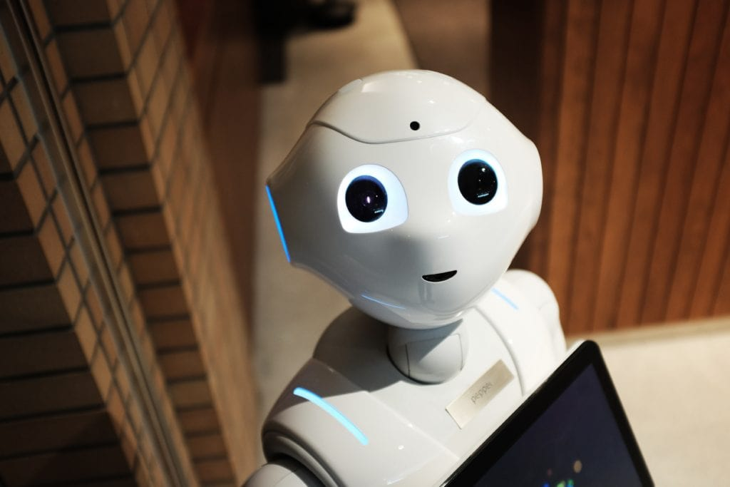 A picture of a white human-like robot with large eyes and an inquisitive expression.