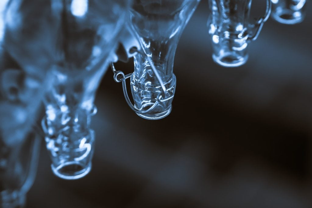 an image of clear glass beverage bottles in a manufacturing plant