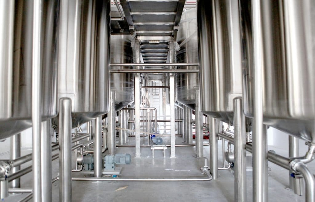 a picture of stainless steel vats in a food and beverage manufacturing facility