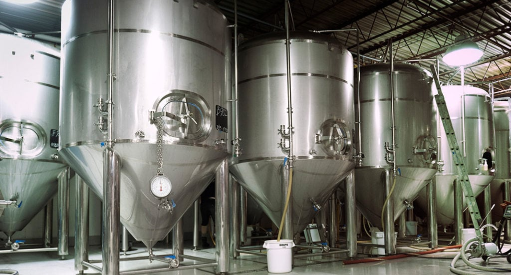 A picture of several vats in a brewery.