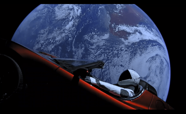 a still of the starman mannequin and tesla roadster with earth in the background from the SpaceX.com live feed..