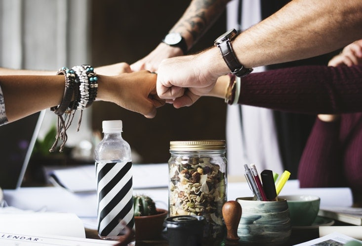 A photo of people bringing their hands together as a sign of teamwork.
