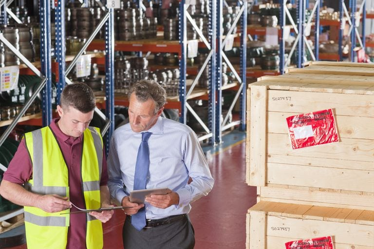 a picture of two warehouse workers comparing shipment documents.