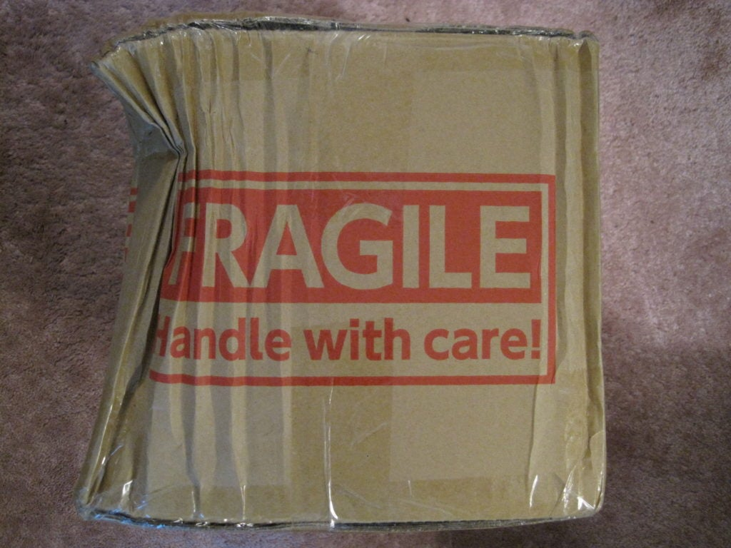 A picture of a heavily damaged package labeled fragile - handle with care.