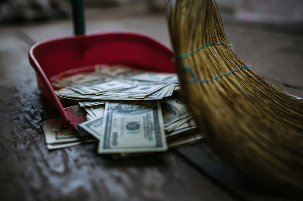a picture of a broom sweeping money into a dustpan.