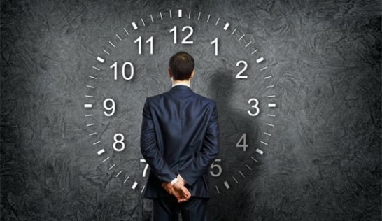 a picture of a man in a suit standing in front of a large clock face.