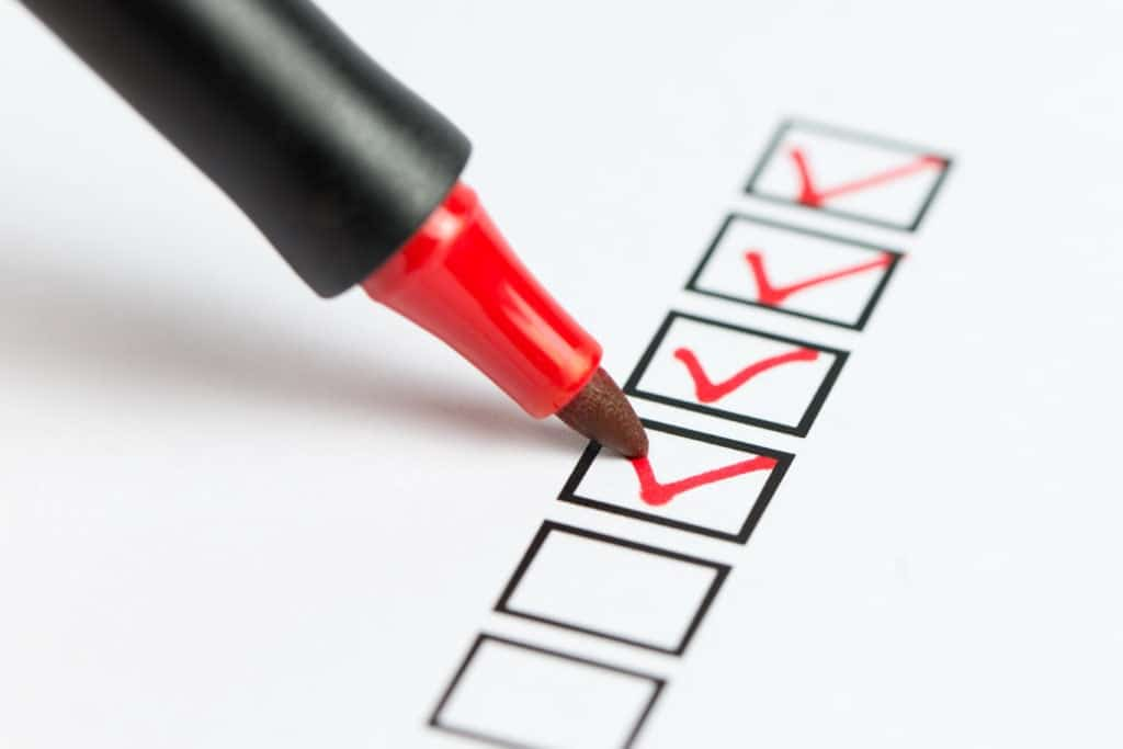 a photo of a checklist being marked with a red pen.