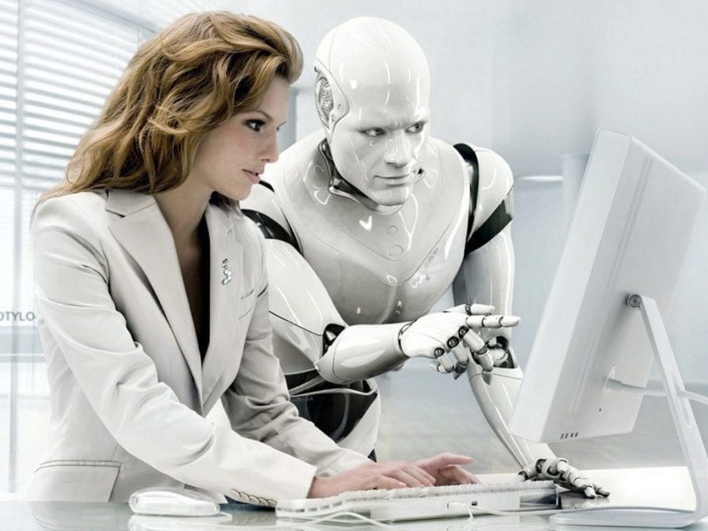 a photo of a human and a robot discussing information on a computer monitor