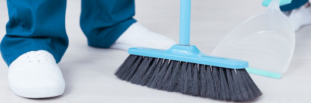 an image of a cleaning crew sweeping into a dust pan.
