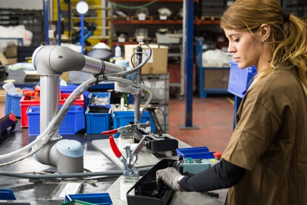 A picture of a worker and cobot working in manufacturing facility.