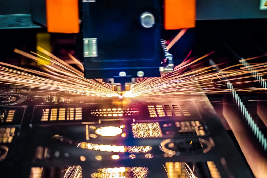 A photo of a CNC machine cutting metal shapes and forms where data is fed from an ERP system.
