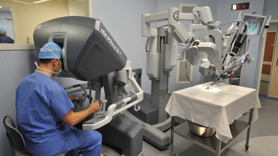 a photo of a curgeon and collaborative robot practicing in an operating room.
