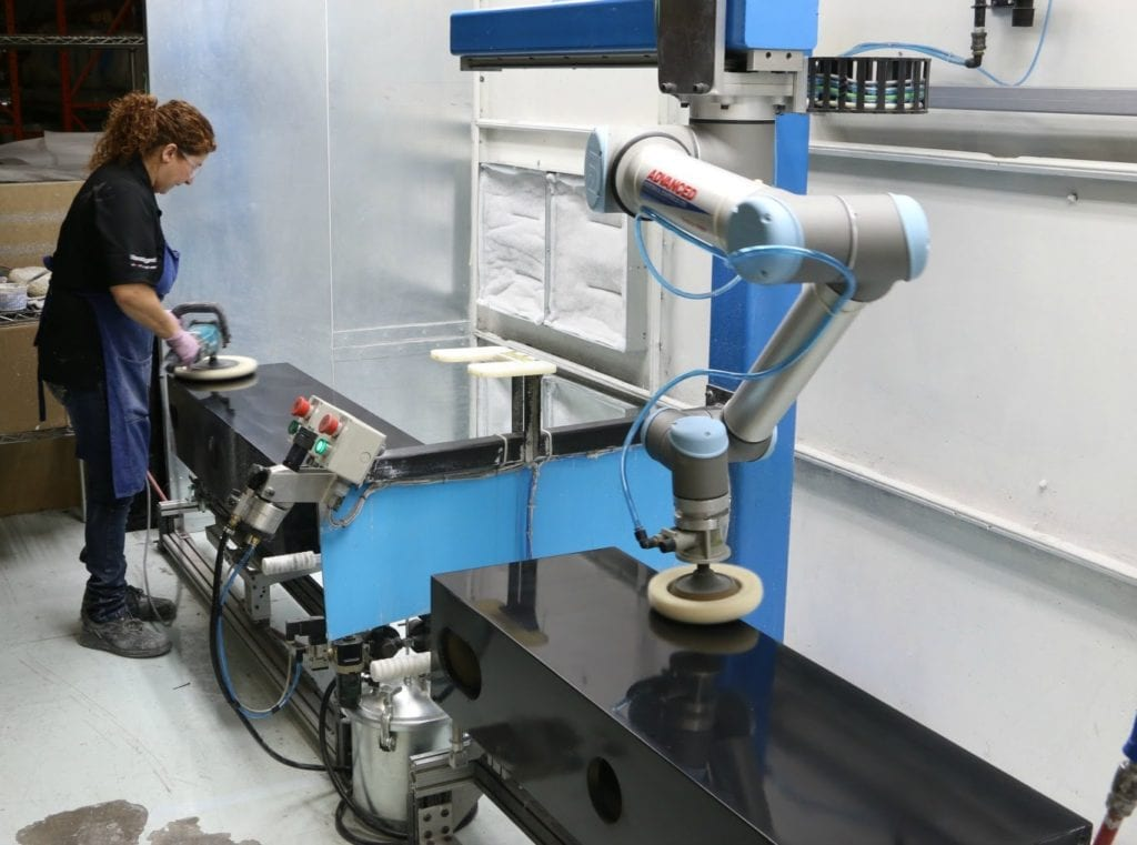 a photo of a woman working alongside a robot to polish speaker cabinets. industry 5.0 collaborative robotics at work.