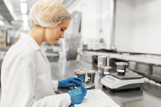 An image of a technician lab testing food samples, a task food and beverage manufacturing ai can make easier.