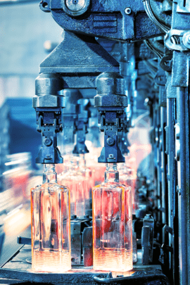 A photograph of bottle being manufactured before labeling and application of mass personalization technology